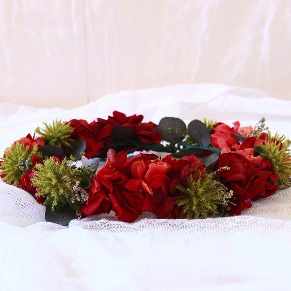 corona con flores preservadas con hortensias rojas